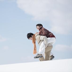 雪原でおんぶをするカップルの写真素材 [FYI04553834]