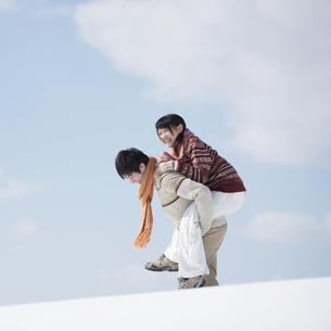 雪原でおんぶをするカップルの写真素材 [FYI04553835]