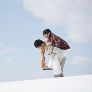 雪原でおんぶをするカップルの写真素材 [FYI04553836]