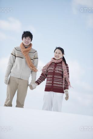 雪原で手をつなぐカップルの写真素材 [FYI04553853]