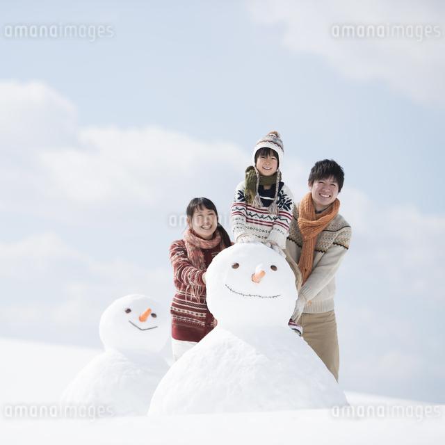 雪だるまの側で微笑む家族の写真素材 [FYI04553887]