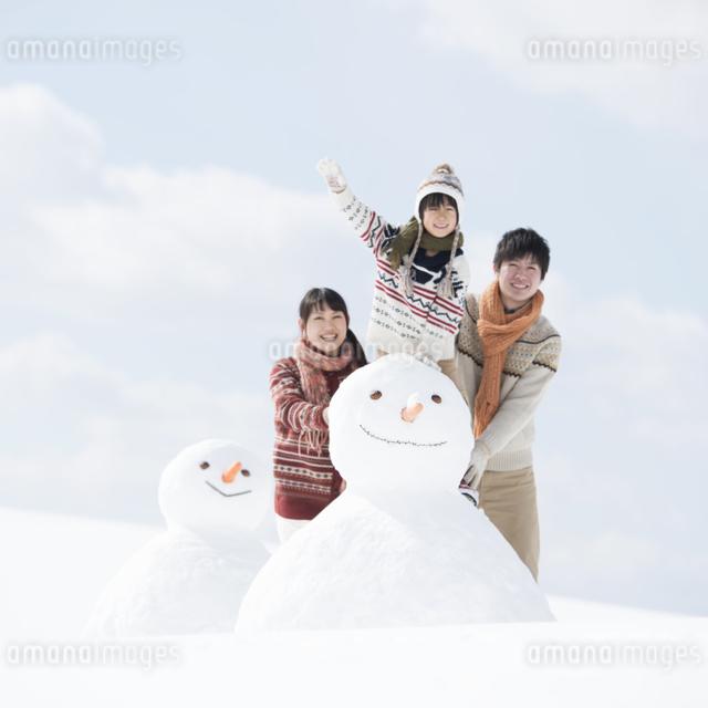 雪だるまの側で微笑む家族の写真素材 [FYI04553889]