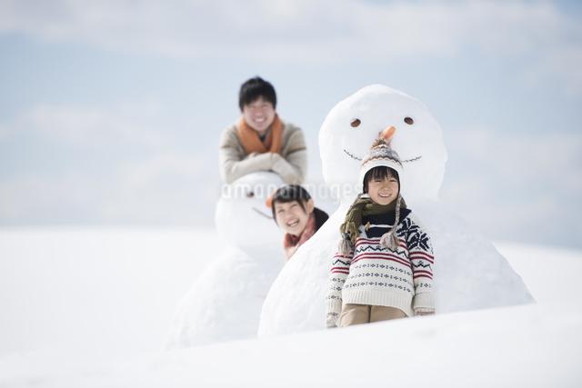 雪だるまの側で微笑む家族の写真素材 [FYI04553904]