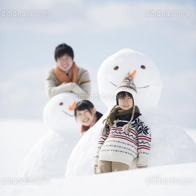 雪だるまの側で微笑む家族の写真素材 [FYI04553911]