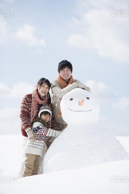 雪だるまの側で微笑む家族の写真素材 [FYI04553917]