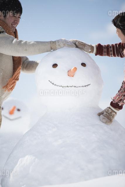 雪だるまを作るカップルの写真素材 [FYI04553940]