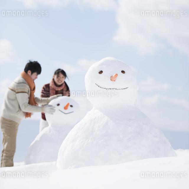 雪だるまを作るカップルの写真素材 [FYI04553947]