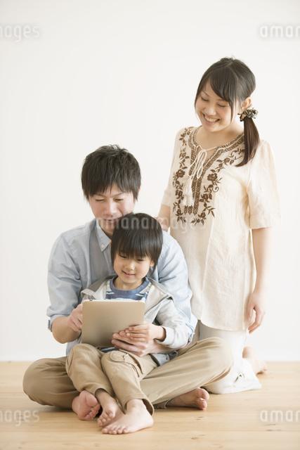 タブレットPCを見る家族の写真素材 [FYI04553996]