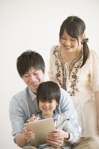 タブレットPCを見る家族の写真素材 [FYI04554000]