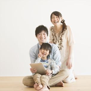 タブレットPCを持ち微笑む家族の写真素材 [FYI04554004]