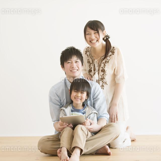 タブレットPCを持ち微笑む家族の写真素材 [FYI04554006]