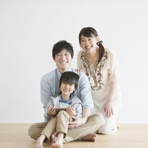 タブレットPCを持ち微笑む家族の写真素材 [FYI04554007]