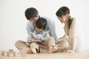 タブレットPCを見る家族の写真素材 [FYI04554011]