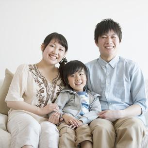 ソファに座り微笑む家族の写真素材 [FYI04554042]