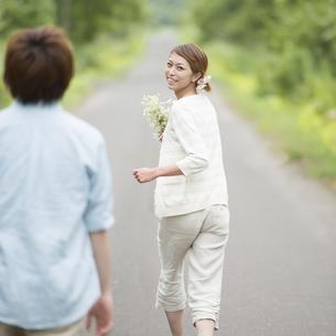一本道を走るカップルの写真素材 [FYI04554058]