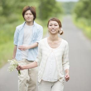 一本道を走るカップルの写真素材 [FYI04554059]