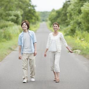 一本道を歩くカップルの写真素材 [FYI04554079]