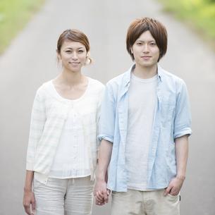 一本道で手をつなぎ微笑むカップルの写真素材 [FYI04554090]