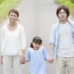 一本道で手をつなぎ微笑む親子の写真素材 [FYI04554093]