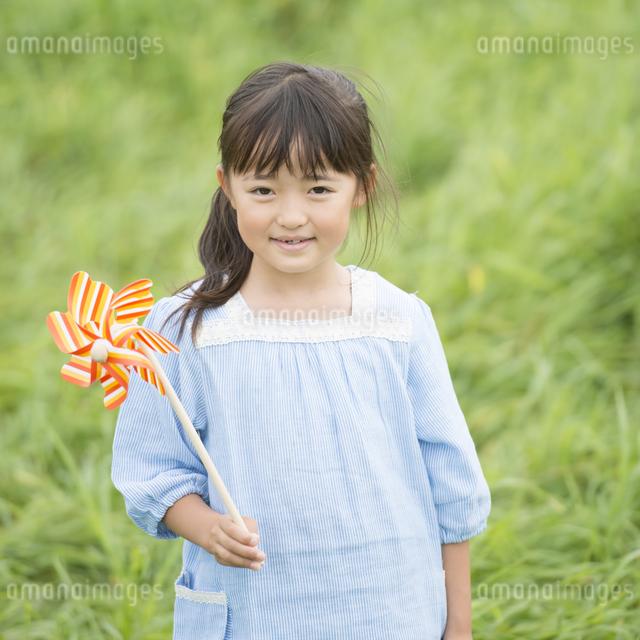草原で風車を持ち微笑む女の子の写真素材 [FYI04554107]