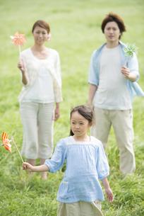 草原で風車を持ち微笑む親子の写真素材 [FYI04554112]