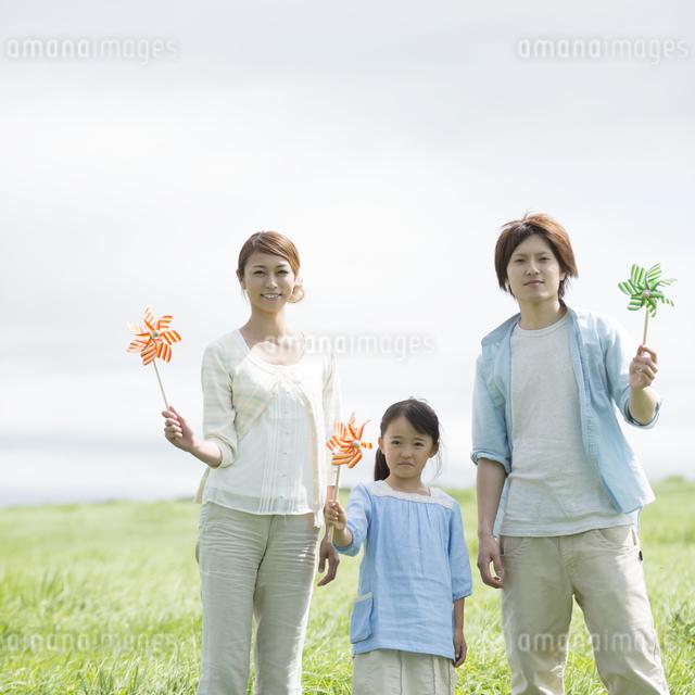草原で風車を持ち微笑む親子の写真素材 [FYI04554120]