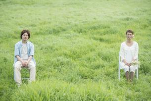 草原で椅子に座り微笑むカップルの写真素材 [FYI04554134]