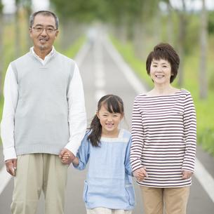 手をつなぎ微笑む祖父母と孫の写真素材 [FYI04554154]