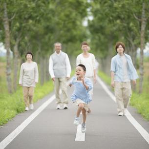 走る女の子を見守る家族の写真素材 [FYI04554168]