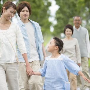 手をつなぎ微笑む親子と見守る家族の写真素材 [FYI04554173]