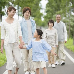 一本道を歩く3世代家族の写真素材 [FYI04554175]