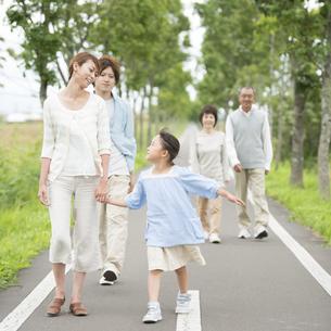一本道を歩く3世代家族の写真素材 [FYI04554179]