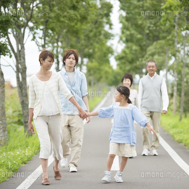 一本道を歩く3世代家族の写真素材 [FYI04554181]