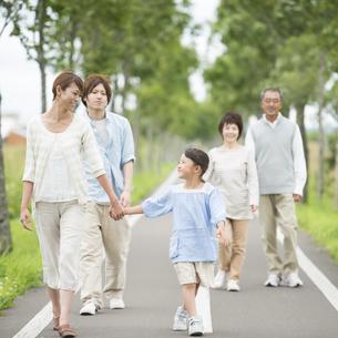 一本道を歩く3世代家族の写真素材 [FYI04554182]