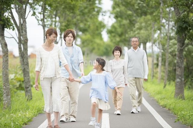 一本道を歩く3世代家族の写真素材 [FYI04554184]