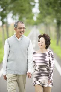 手をつなぎ一本道を歩くシニア夫婦の写真素材 [FYI04554199]