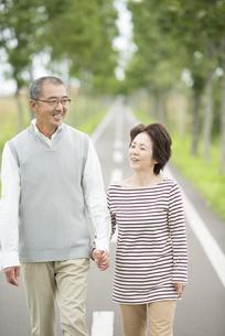 手をつなぎ一本道を歩くシニア夫婦の写真素材 [FYI04554200]