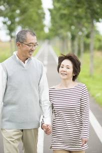 手をつなぎ一本道を歩くシニア夫婦の写真素材 [FYI04554201]