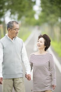 手をつなぎ一本道を歩くシニア夫婦の写真素材 [FYI04554202]
