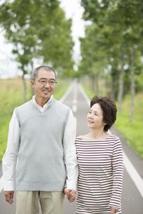 手をつなぎ一本道を歩くシニア夫婦の写真素材 [FYI04554205]