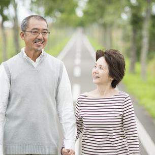 手をつなぎ一本道を歩くシニア夫婦の写真素材 [FYI04554207]