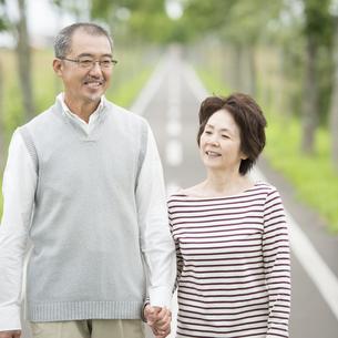 手をつなぎ一本道を歩くシニア夫婦の写真素材 [FYI04554209]