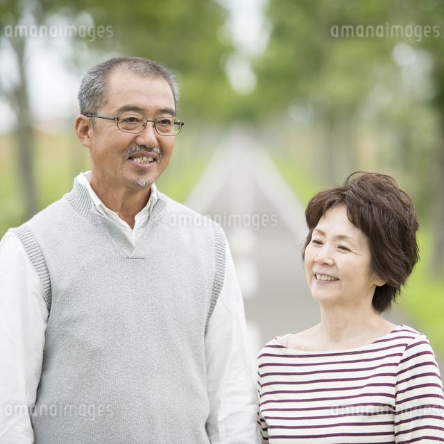 一本道で微笑むシニア夫婦の写真素材 [FYI04554211]