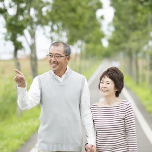 手をつなぎ一本道を歩くシニア夫婦の写真素材 [FYI04554212]