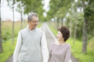 一本道を歩くシニア夫婦の写真素材 [FYI04554215]