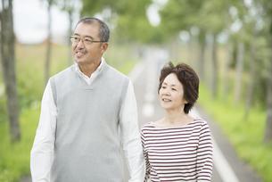 一本道を歩くシニア夫婦の写真素材 [FYI04554216]