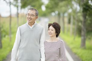 一本道を歩くシニア夫婦の写真素材 [FYI04554218]