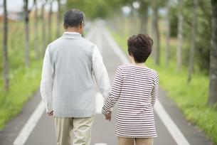 手をつなぎ一本道を歩くシニア夫婦の後姿の写真素材 [FYI04554222]