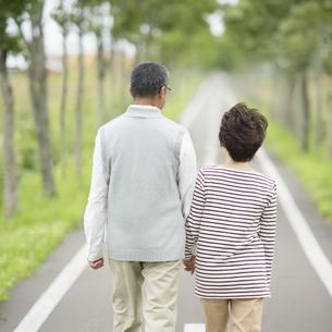 手をつなぎ一本道を歩くシニア夫婦の後姿の写真素材 [FYI04554224]