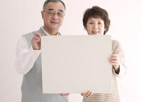 メッセージボードを持ち微笑むシニア夫婦の写真素材 [FYI04554226]